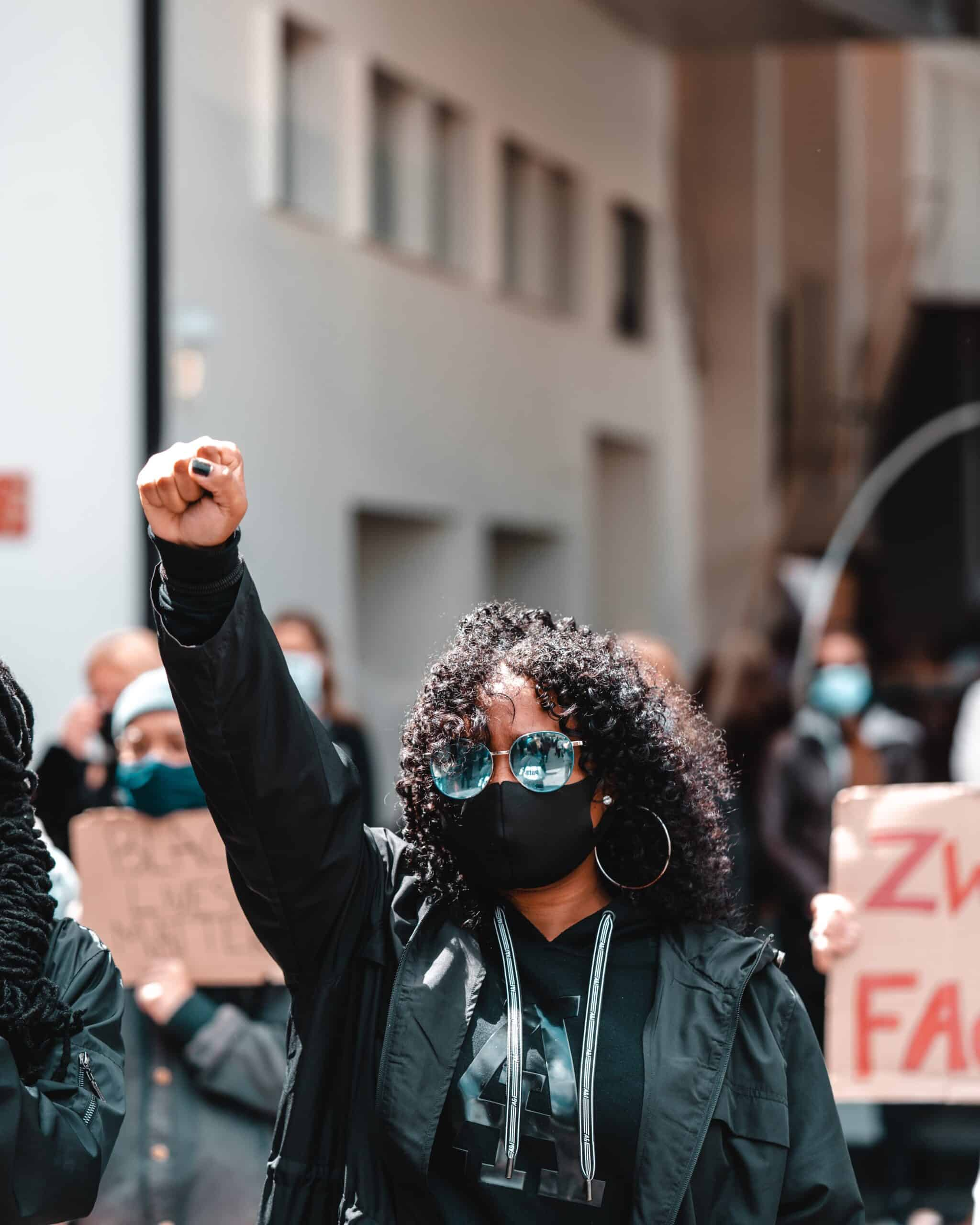 Image of brown skinned woman with blue shades and shoulder length curly dark hair with fist raised amidst crowd of protesters